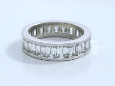 Diamond eternity band with twenty-one emerald cut diamonds with 5.31 total carat weight channel-set in a platinum band