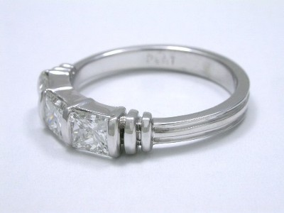 Diamond and platinum wedding band with three bar set rectangular princess cut diamonds, double flanking bars, and channeled shank