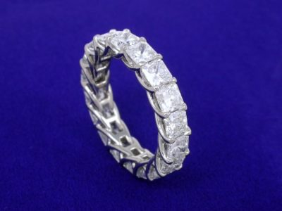 Trellis-style band with shared-prong set square radiant diamonds