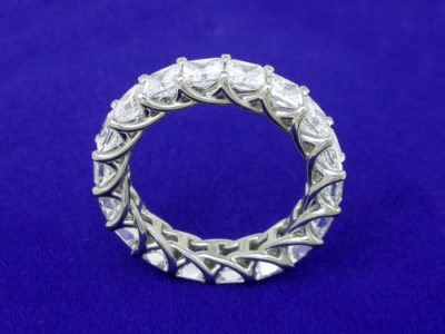 Eternity band with 18 shared-prong set square radiant cut diamonds (4.84 total carat weight) in trellis-style shank