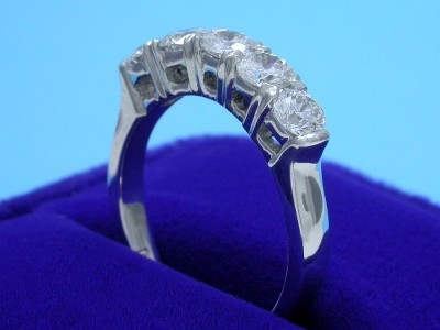 Diamond and platinum wedding band with five shared prong set round brilliant diamonds