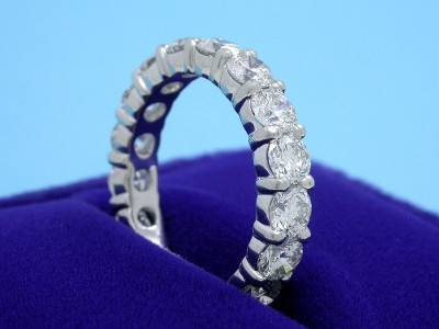 Custom platinum diamond wedding band with shared prong set round brilliant cut diamonds