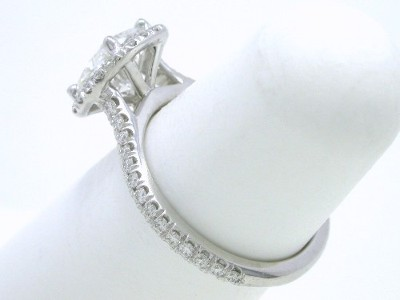French pave-set round brilliant cut diamonds in a halo around the cushion diamond and three-fourths the way down the top of the cathedral-style shank