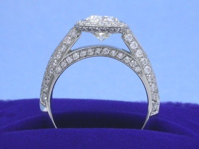120 pave-set round diamonds (0.95 total carat weight) surrounding the round diamond in a knife edge style, on the bridge, and in two rows going half way down the shank.