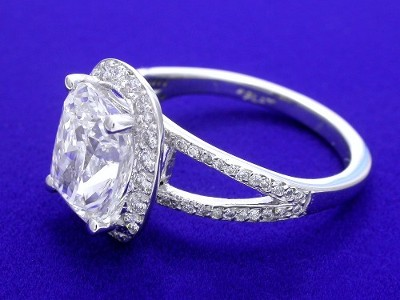pave-set round diamonds surrounding the prong-set cushion center diamond, and going half-way down the top of the split-shank