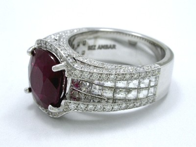 Cushion cut red ruby prong set in Bez Ambar designer 18-karat white-gold mounting with pave diamonds on the knife-edge frame and flanking Blaze cut diamonds on the shank