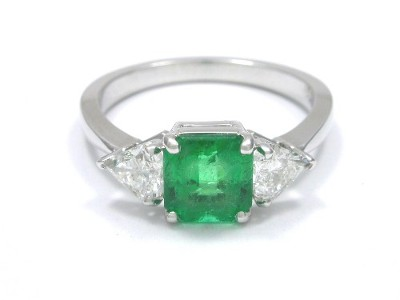 Emerald cut Colombian emerald prong set in a 14-karat white-gold three-stone mounting with kite shaped diamond side stones