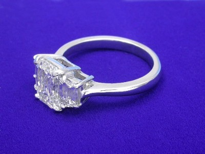 Custom platinum three stone mounting with a pair of matched step-cut trapezoid diamonds