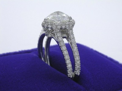 Custom 14-karat white-gold three-prong halo-style mounting with 0.95 tcw pave diamonds around the center stone and going half way down the split shank