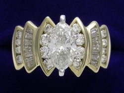 1.29 carat Marquise Cut diamond ring with 1.00 tcw of round and baguette diamonds in a yellow gold mounting.