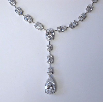Diamond necklace with graduated ovals brilliant cut diamonds and one pear shaped diamond prong-set in custom platinum basket-style necklace mounting