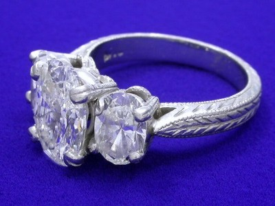 Oval diamond set in a platinum three stone mounting with a pair of matched oval brilliant diamonds