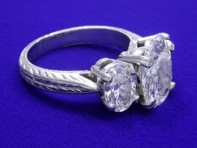 Basket set oval diamond in a platinum three stone mounting with a pair of matched oval brilliant diamonds
