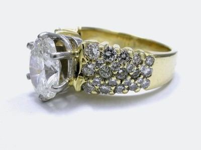 Oval cut diamond prong set in a platinum 6-prong head on a 14-karat yellow gold shank with 46 pave-set round diamonds having 1.11 total carat weight