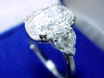 Custom platinum three-stone mounting with a pair of matched heart brilliant cut diamonds