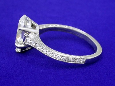 Custom platinum mounting with 5-prong basket and cathedral style shank with graduated pave-set round brilliant cut diamonds between milgrain edging and hand engraved sides going three-fourths the way down the shank
