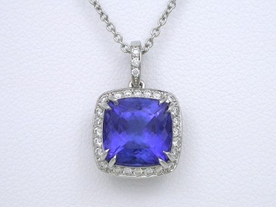 3.15 carat cushion shaped Tanzanite double prong set in a white gold mounting with pave knife-edge frame and pave on the flexible single bail