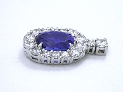 Oval shaped Tanzanite pendant with prong set round diamonds around the Tanzanite and on the bail
