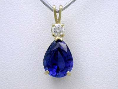 Pear shaped Blue Sapphire pendant with round diamond prong set on the double bail