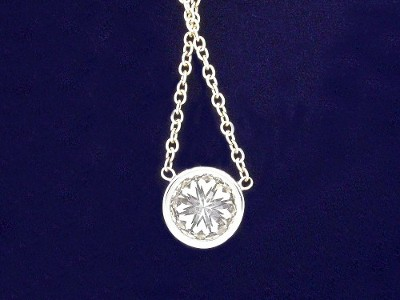 Round brilliant cut diamond bezel set in barrel style pendant mounting with fixed chain