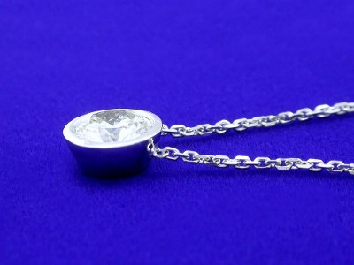 Round brilliant cut diamond bezel set in bezel-style pendant mounting with fixed chain