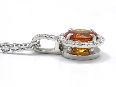Round cut orange-colored sapphire prong set in pendant mounting with pave halo and pave single bail