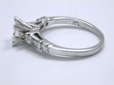 Princess cut diamond engagement ring with tapered baguette and round diamonds on the shank