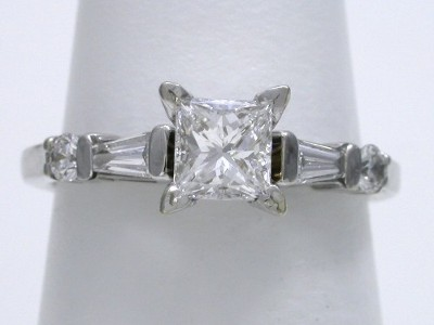 Princess cut diamond ring with two bar-set tapered baguette diamonds and two bar-set round brilliant diamonds going half way down the shank