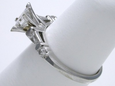 Mounting has two bar-set tapered baguette diamonds and two bar-set round brilliant diamonds going half way down the shank