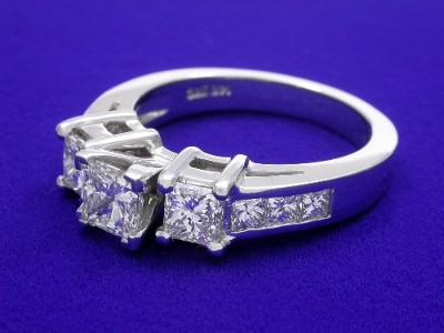 Princess cut diamond ring is set with a pair of matched princess cut diamonds in basket heads and six channel-set princess cut diamonds going half way down the shank