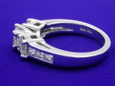 Princess cut diamond engagement ring with a pair of basket set princess cut diamonds and six channel-set princess cut diamonds going half way down the shank