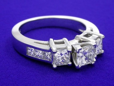 Princess cut diamond engagement ring with princess cut side diamonds and channel-set princess cut diamonds on the shank