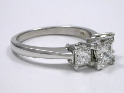 Diamond ring with three princess cut diamons in basket style mounting