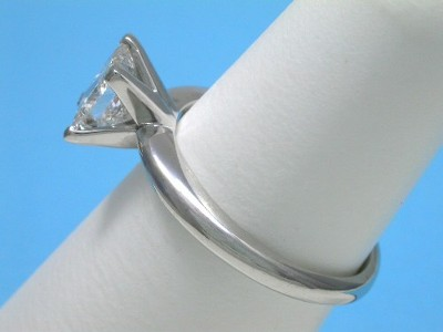 Princess cut diamond ring with platinum  mounting with four-prong head and knife-edge style shank