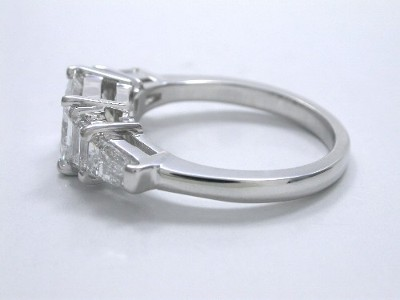 Princess cut diamond ring with custom 14-karat white gold five stone mounting with a pair of matched step-cut trapezoid diamonds and a matched pair of step-cut tapered baguette diamonds in basket style heads