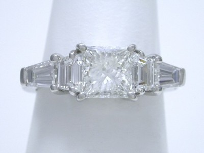 Princess cut diamond ring with step cut trapezoids and tapered baguettes