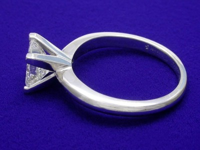 Princess cut diamond engagement ring with 14-karat white-gold mounting featuring four-prong solitaire-style head and knife-edge style shank