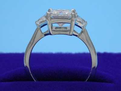 Princess cut diamond ring with custom platinum three stone mounting with a pair of matched trillion cut diamonds