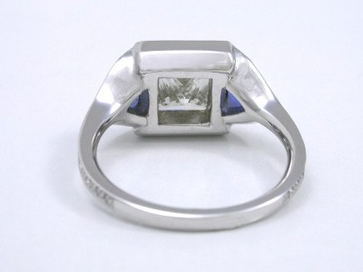 Princess diamond ring with custom 18-karat white-gold bezel set mounting with a pair of matched bezel-set medium blue sapphire trillions and pave set diamonds  surrounding all three stones and going three quarters the way down the shank