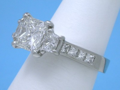 Princess cut diamond ring with platinum three-stone basket-style mounting holding pair of brilliant-cut trapezoids and princess cut diamonds channel set in the top of the shank