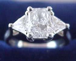 1.03 carat Radiant Cut diamond graded E color, VS2 clarity, with 1.40 ratio set in a platinum mounting with 0.75 tcw of trillion cut side diamonds