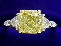 2.06 carat Square Radiant Cut diamond with Fancy Yellow color, VS1 clarity, and 0.40 total carat weight of Trillion side diamonds in platinum and 18-karat yellow gold custom mounting.