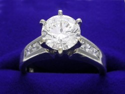 1.70 carat Round Brilliant diamond graded H color SI2 clarity and prong-set in mounting with six Princess cut Diamonds