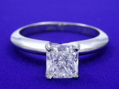 Radiant cut diamond engagement ring with 14-karat white-gold solitaire style mounting with knife-edge shank