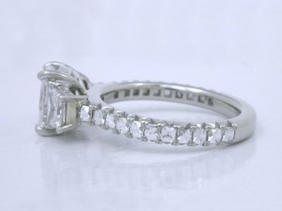 Radiant cut diamond ring with brilliant cut trapezoids side diamonds in modified baskets that accommodate a flush fitting wedding band