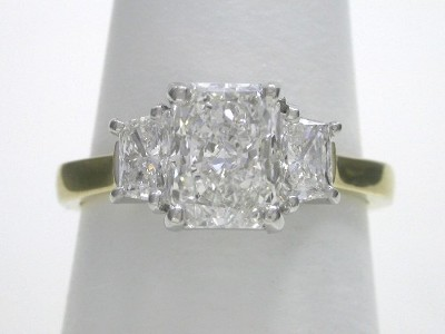 Radiant cut diamond ring with custom 14-karat yellow and white gold three stone mounting with a pair of matched trapezoid diamonds
