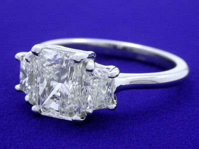 Three stone diamond ring with a 1.20 carat cut cornered rectangular modified brilliant (radiant) cut diamond and matched pair of brilliant trapezoid cut diamonds