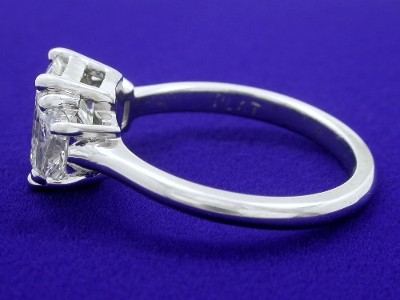 Rectangular radiant cut diamond ring with custom platinum three-stone basket-style mounting with a matched pair of brilliant trapezoid cut diamonds