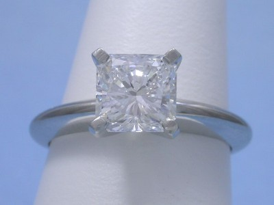 Square radiant cut diamond prong set in platinum solitaire mounting with four-prong style head and knife-edge style shank