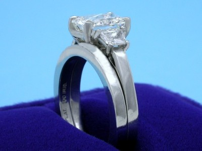 Radiant cut diamond ring with modified basket style accommodates a flush fitting wedding band